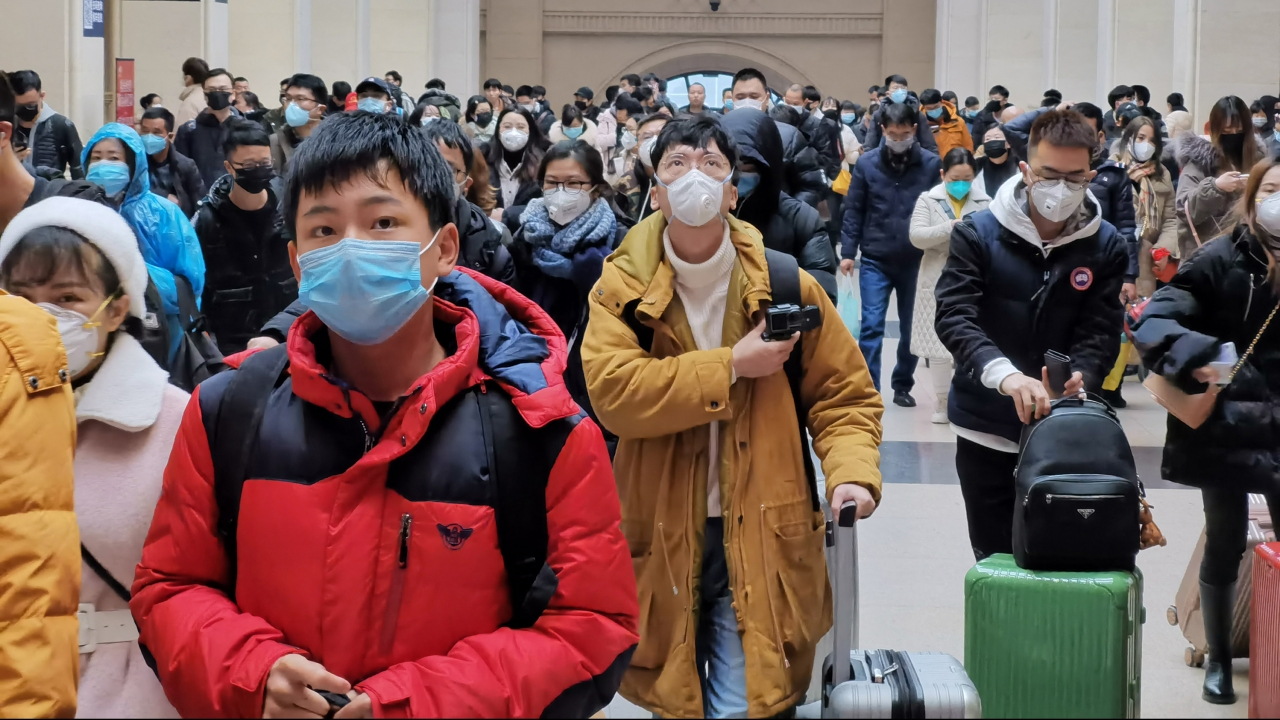 People wear face masks as they wait at a train station in Wuhan, China