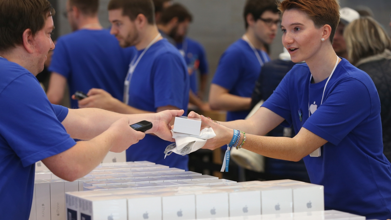 Apple store sales assistants help hand out new iPhones
