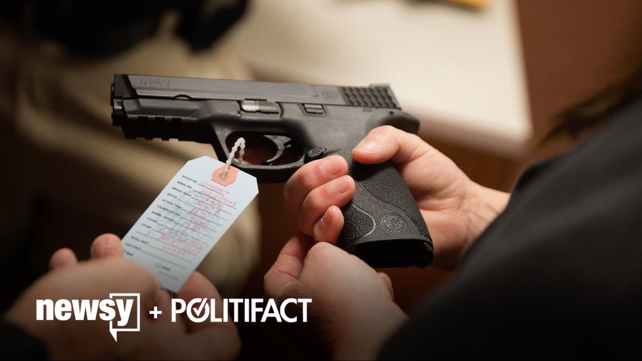 Men look at a gun.