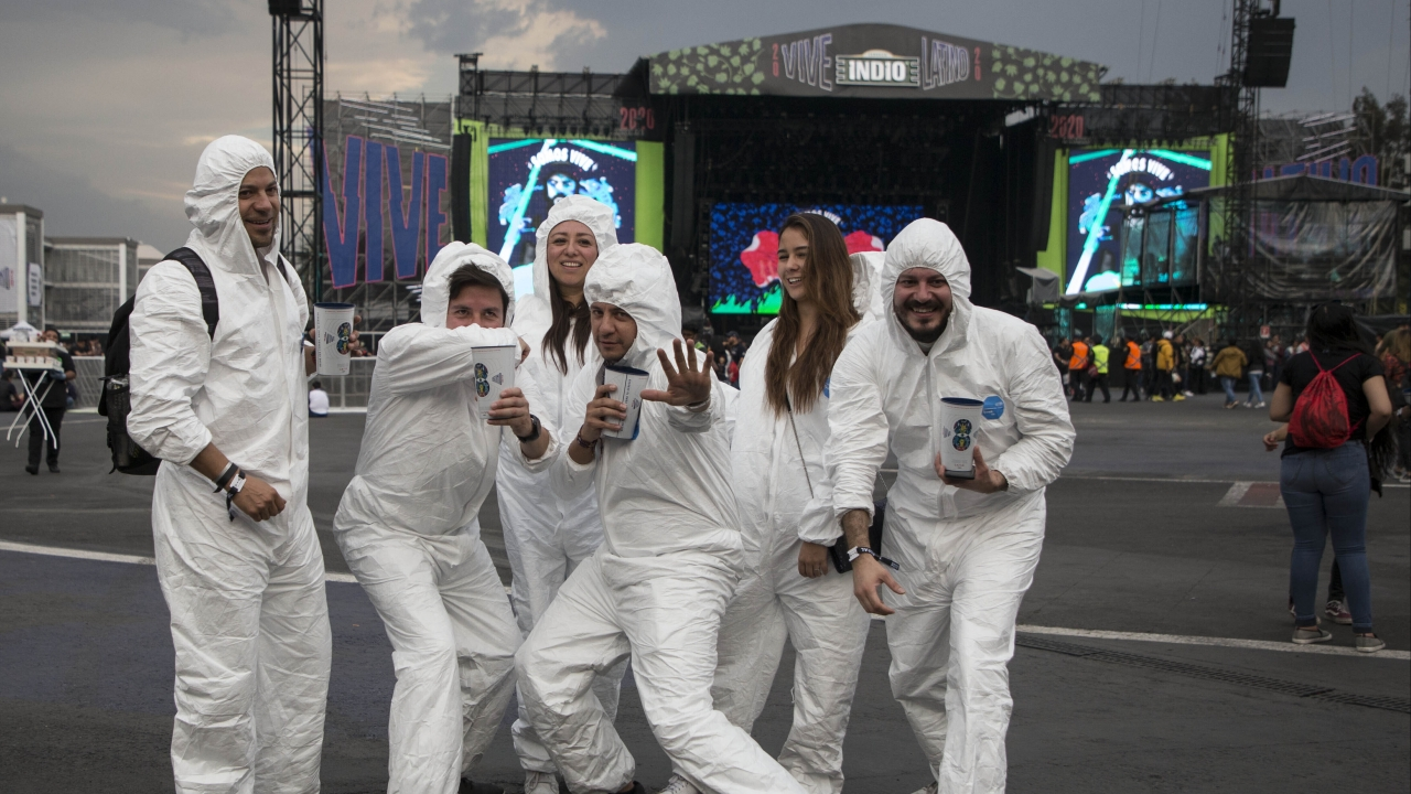 Fans pose in bio suits at March 14 Vive Latino music festival in Mexico, where the president has downplayed the coronavirus.