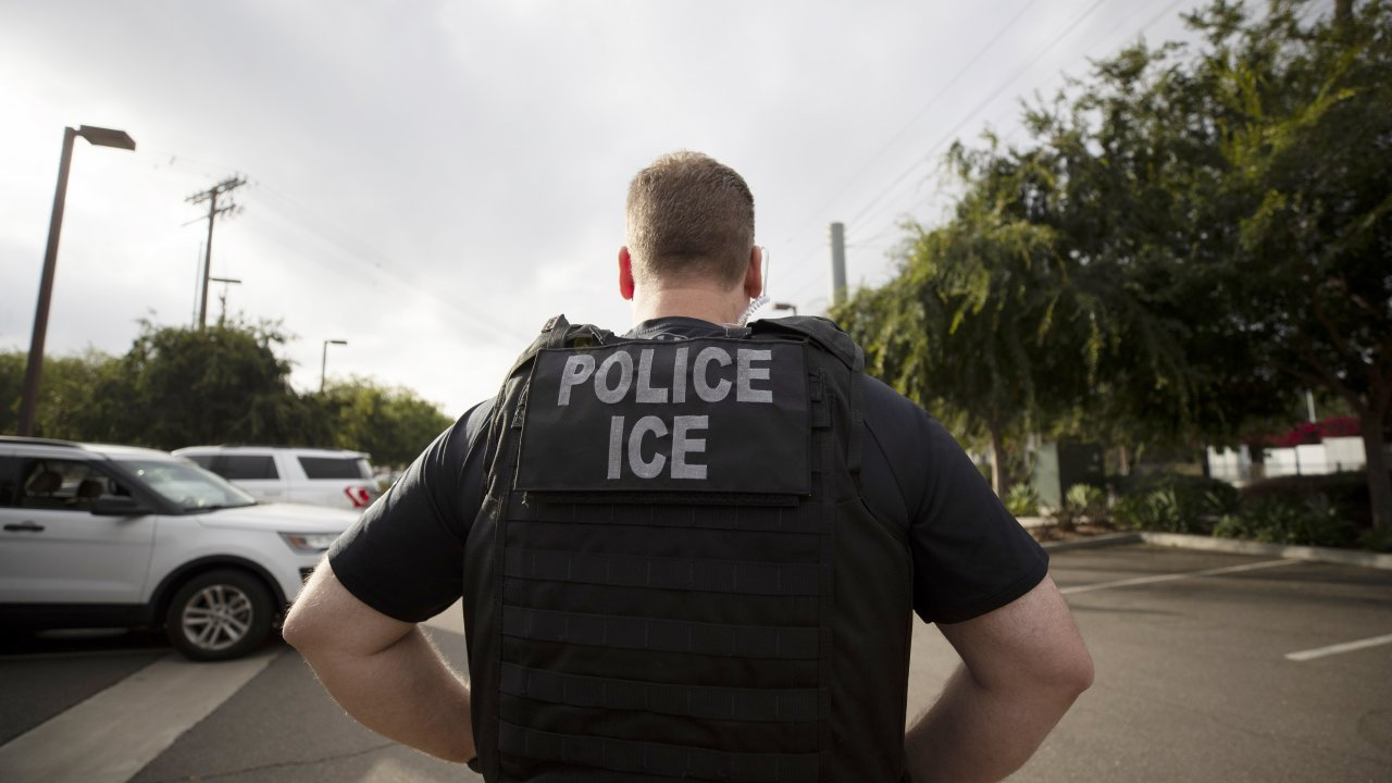 In this July 8, 2019, file photo, an ICE officer looks on during an operation in Escondido, Calif.