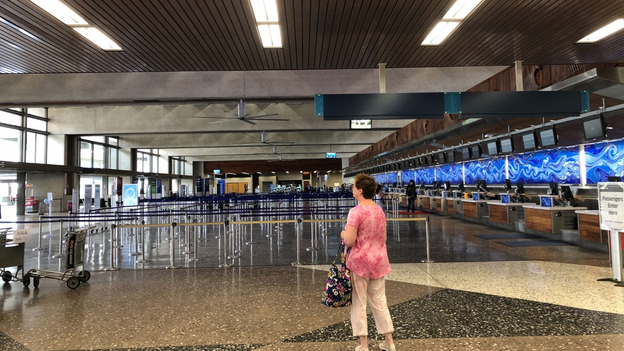 Woman stands at airport in Hawaii