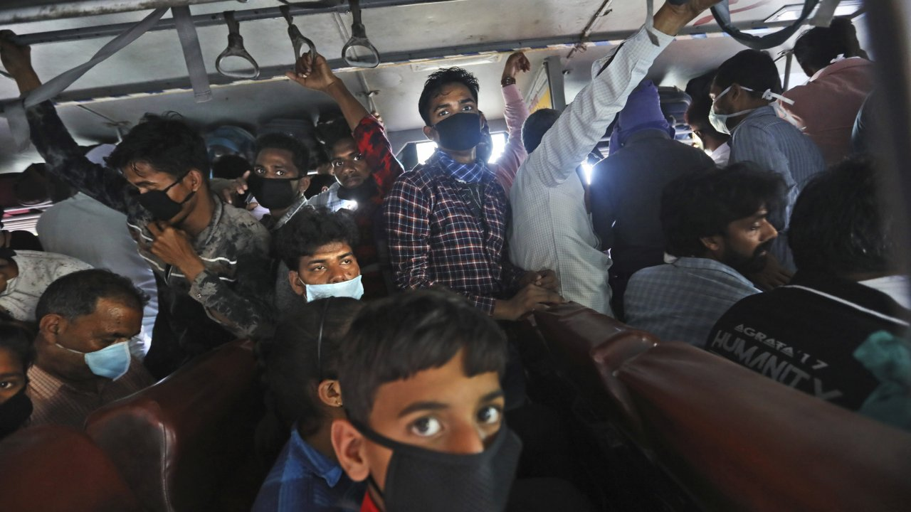 Migrant daily wage laborers crowd a bus in India.