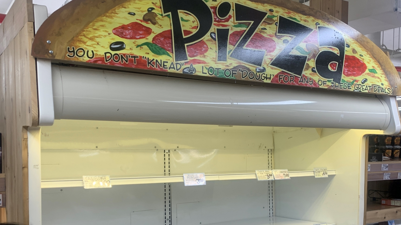Empty shelves of a frozen pizza display