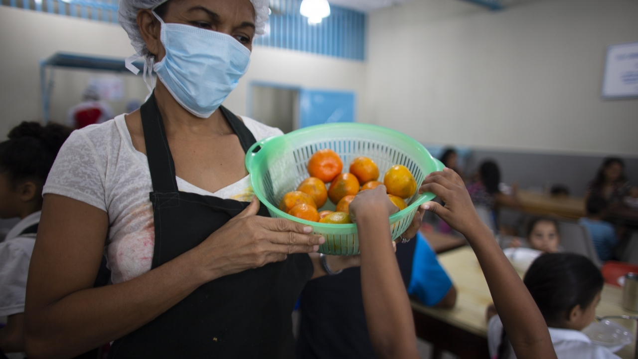 A child reaches for a tangerine at a soup kitchen in Venezuela.