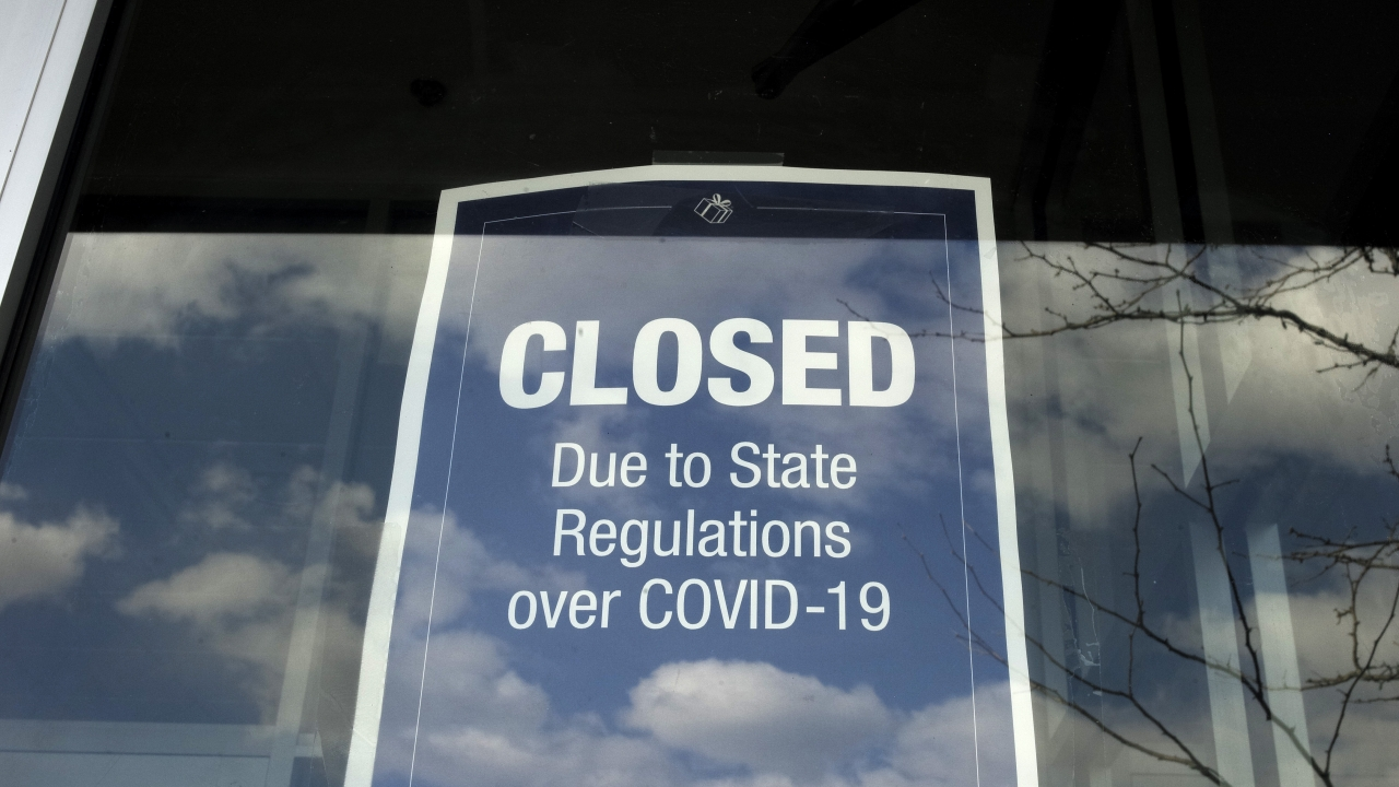 A closed sign is posted in the window of a store because of COVID-19