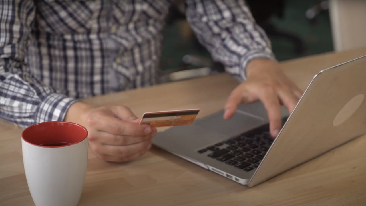 Man types credit card info into computer.