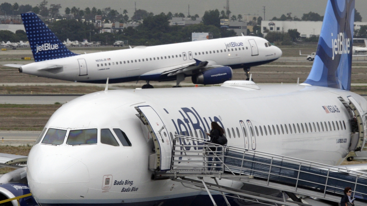 A passenger boards a JetBlue plane.