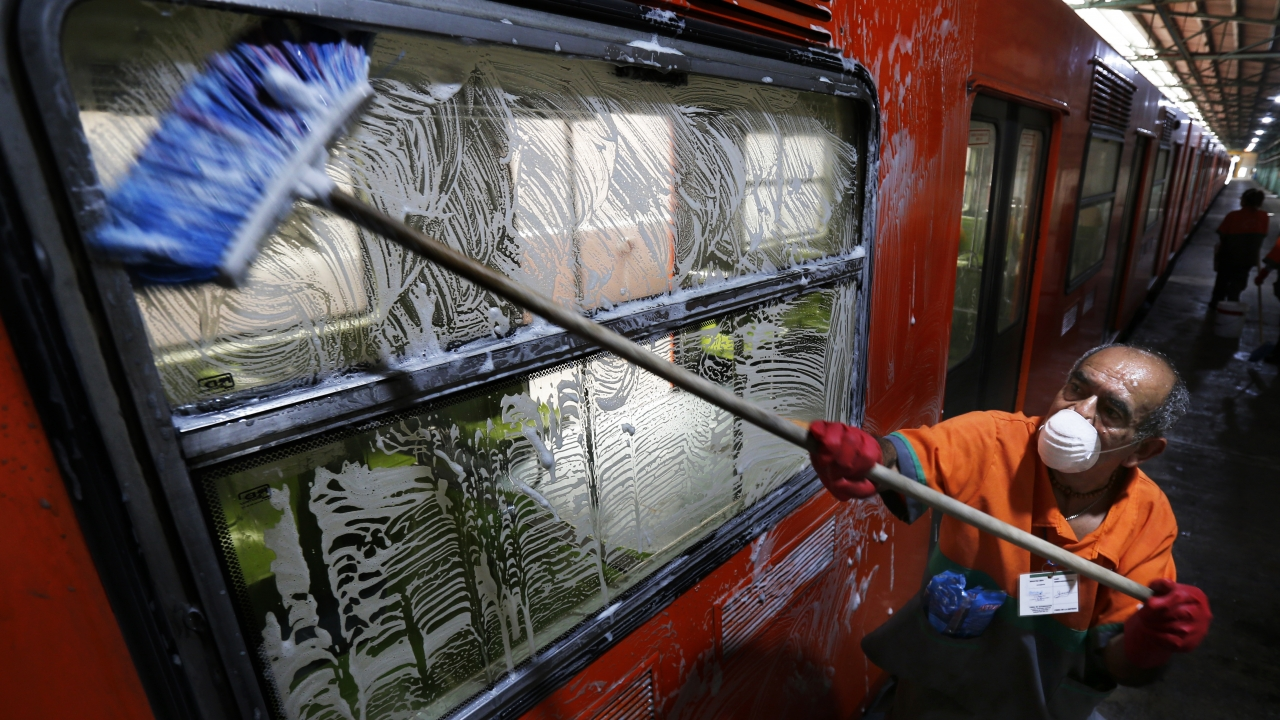 Cleaning Crew member washes subway car in Mexico City.