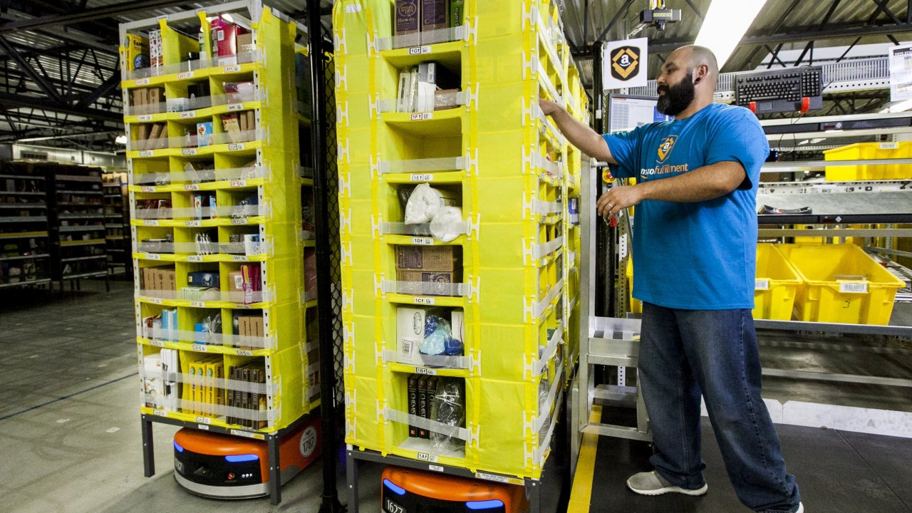 An Amazon employee checks orders at a warehouse