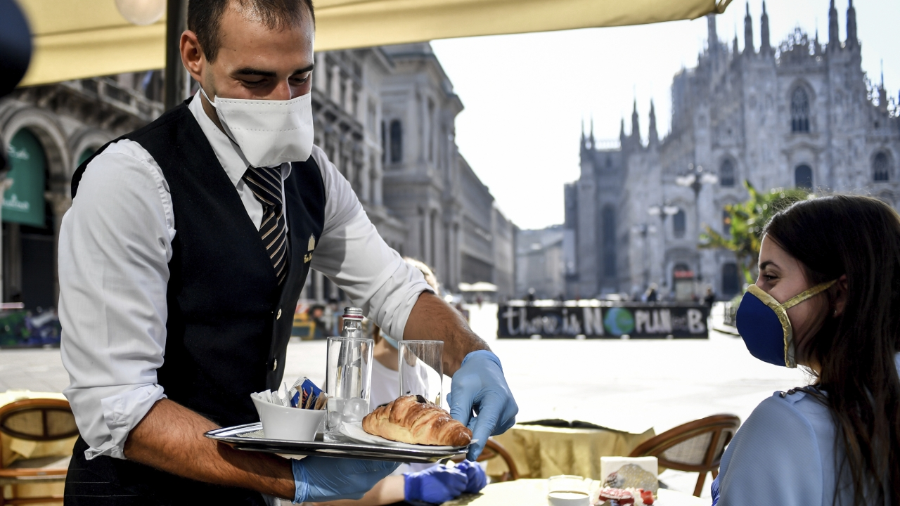 Waiter wearing mask serves breakfast