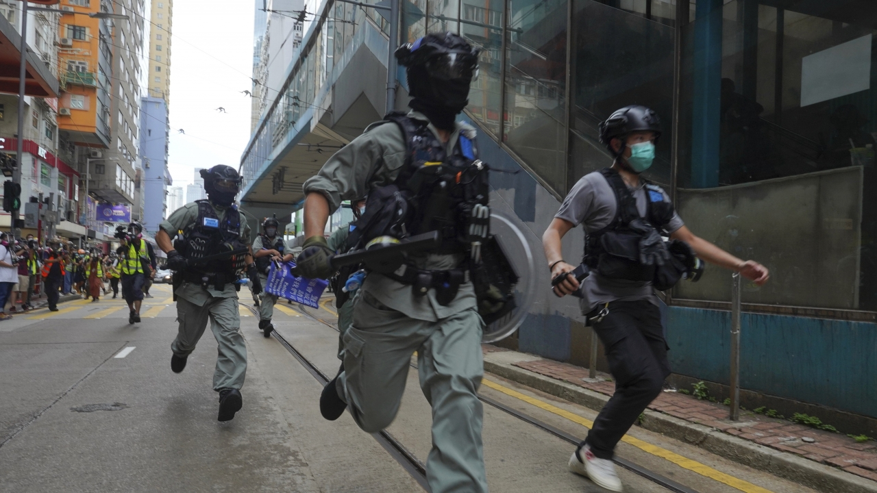 Police chase protesters during the annual handover march in Hong Kong, Wednesday, July. 1, 2020
