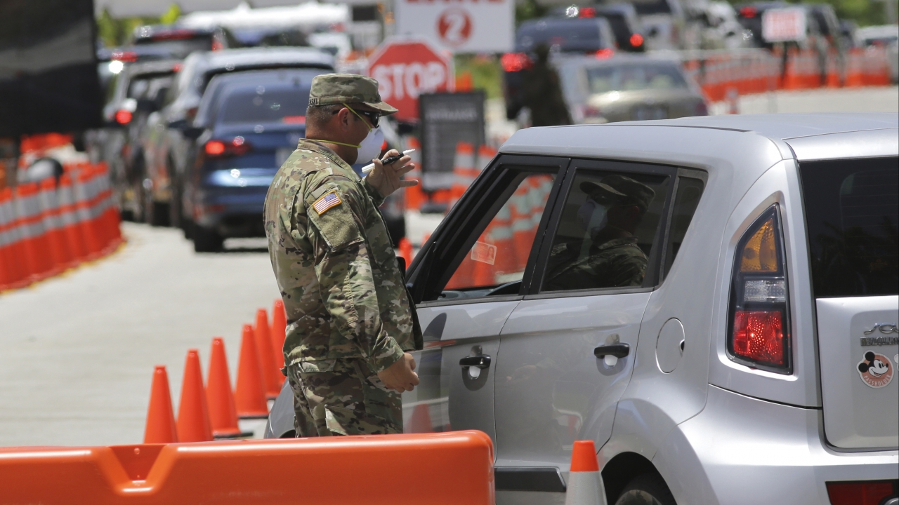 A member of the Florida National Guard talks to a driver as he monitors vehicles entering a testing site for COVID-19.