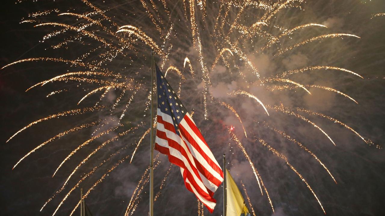 Fireworks explode behind a U.S flag during a July 4th celebration in N.J.