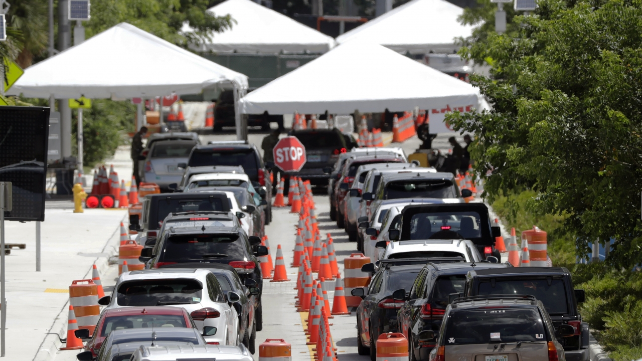 Lines of cars wait at a drive-through coronavirus testing site outside the Miami Beach Convention Center.