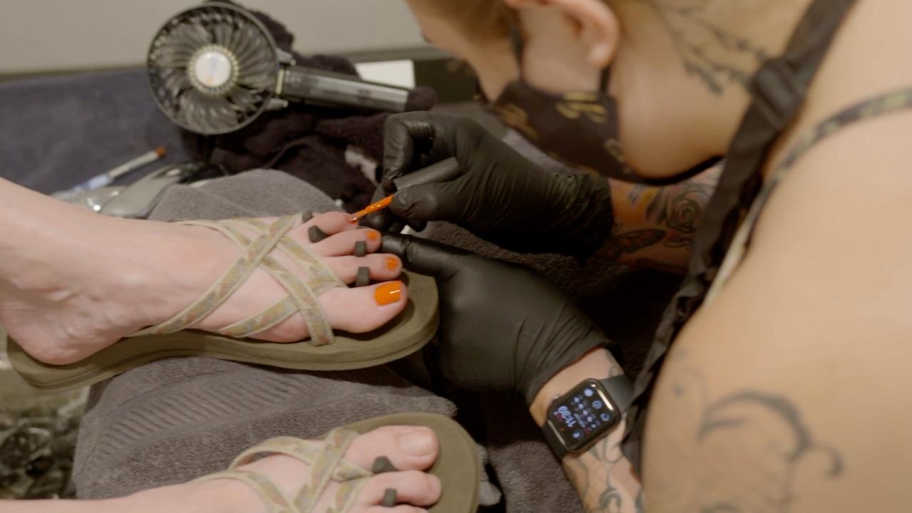 A nail technician giving a pedicure.