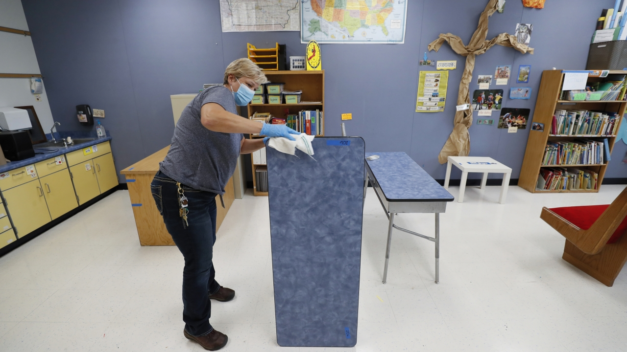 Des Moines Public Schools custodian Cynthia Adams cleans a desk in a classroom at Brubaker Elementary School