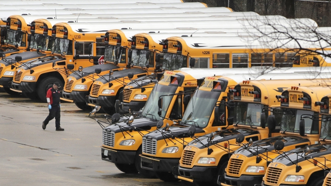 A worker passes public school buses parked at a depot in Manchester, N.H.