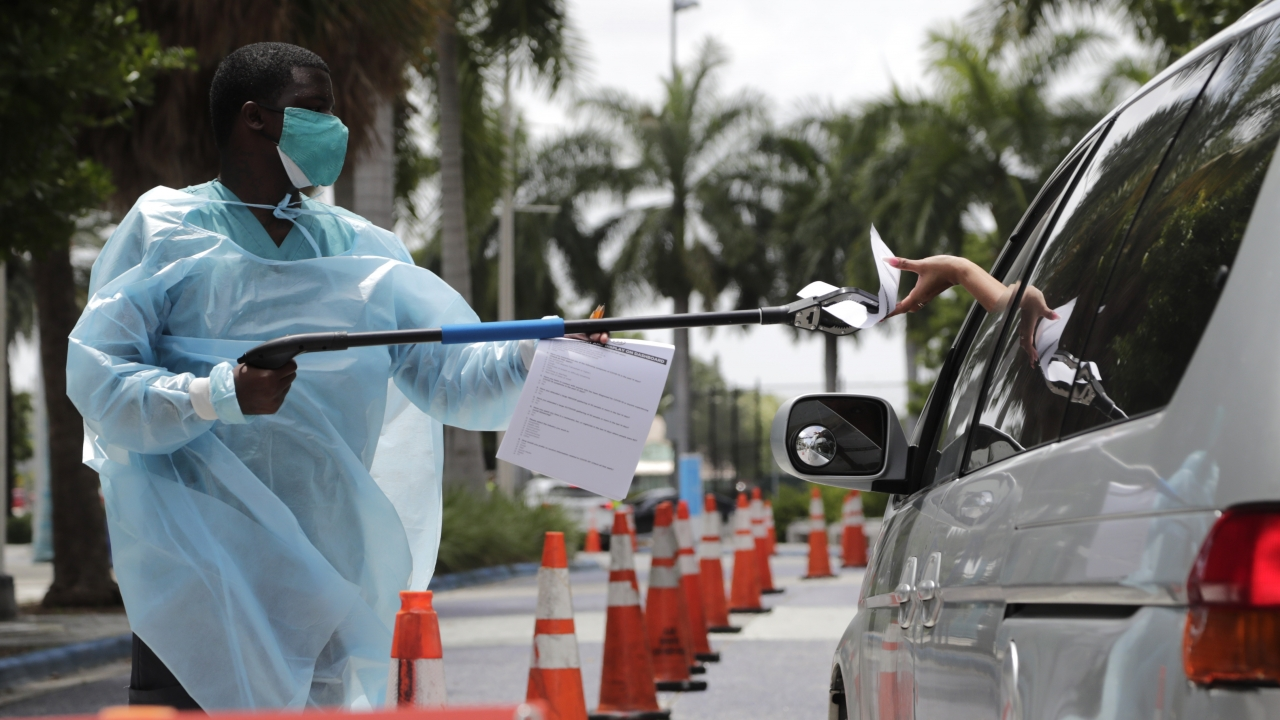 A healthcare worker passes paperwork to a woman in her car