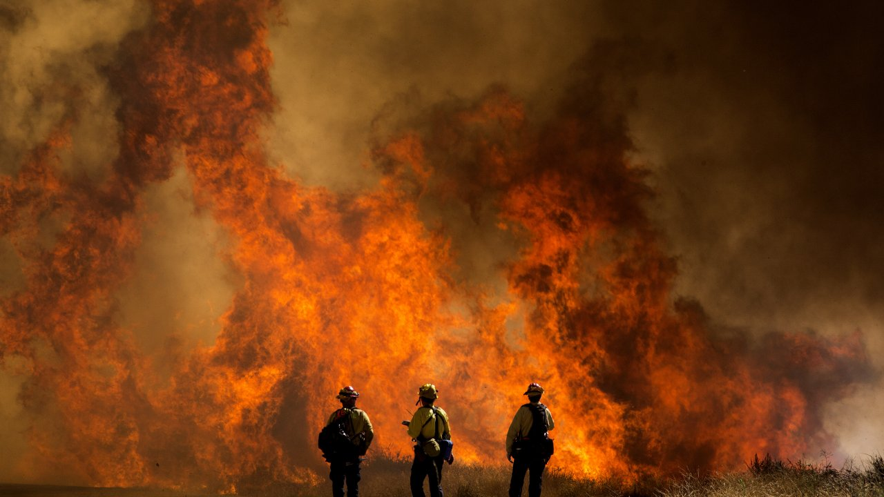 Firefighters watch as the Apple Fire blazes in Southern California.