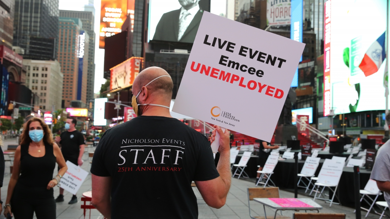 "Man walks across Times Square with sign that says ""LIVE EVENT Emcee UNEMPLOYED."""