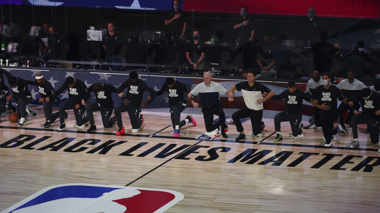 NBA players and coaches lock arms and kneel before an NBA basketball game.