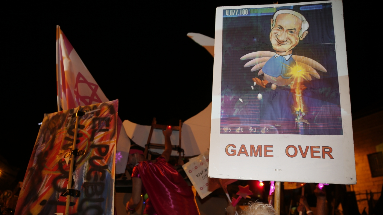 """Protester holds sign with PM Netanyahu's face on it. Below the pictures it says """"Game Over"""""""