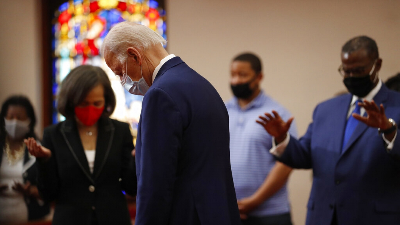 Former Vice President Joe Biden bows his head in prayer during a visit to Bethel AME Church