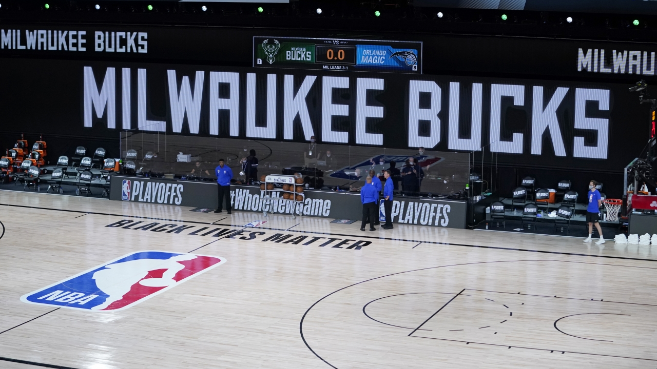 Officials stand by empty court Wednesday after Milwaukee Bucks refuse to take the floor in protest over police shooting.