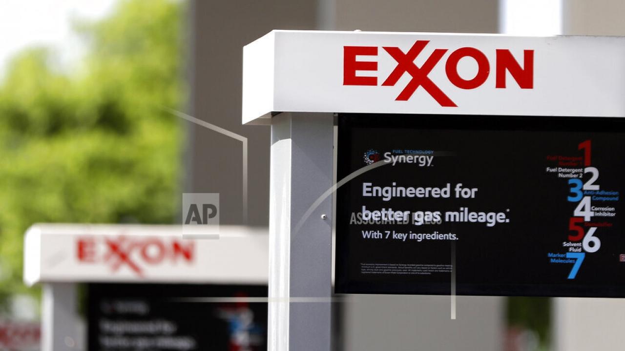 This April 25, 2017, file photo, shows Exxon service station signs in Nashville, Tenn. Exxon Mobil Corp.