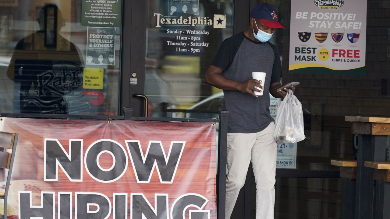 A customer wears a mask and looks at their cell phone as they carry their order past a now hiring sign.