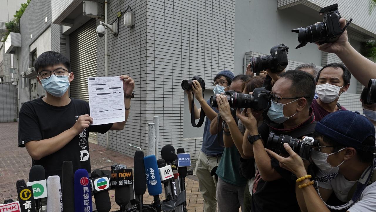 Hong Kong pro-democracy activist Joshua Wong displays a bail paper outside the Central Police Station in Hong Kong.