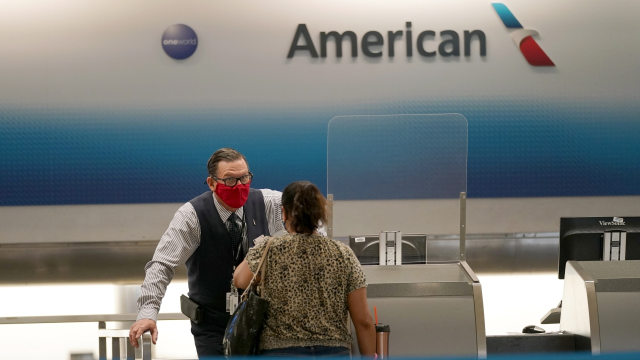 An American Airlines ticket agent works with a customer at Miami International Airport