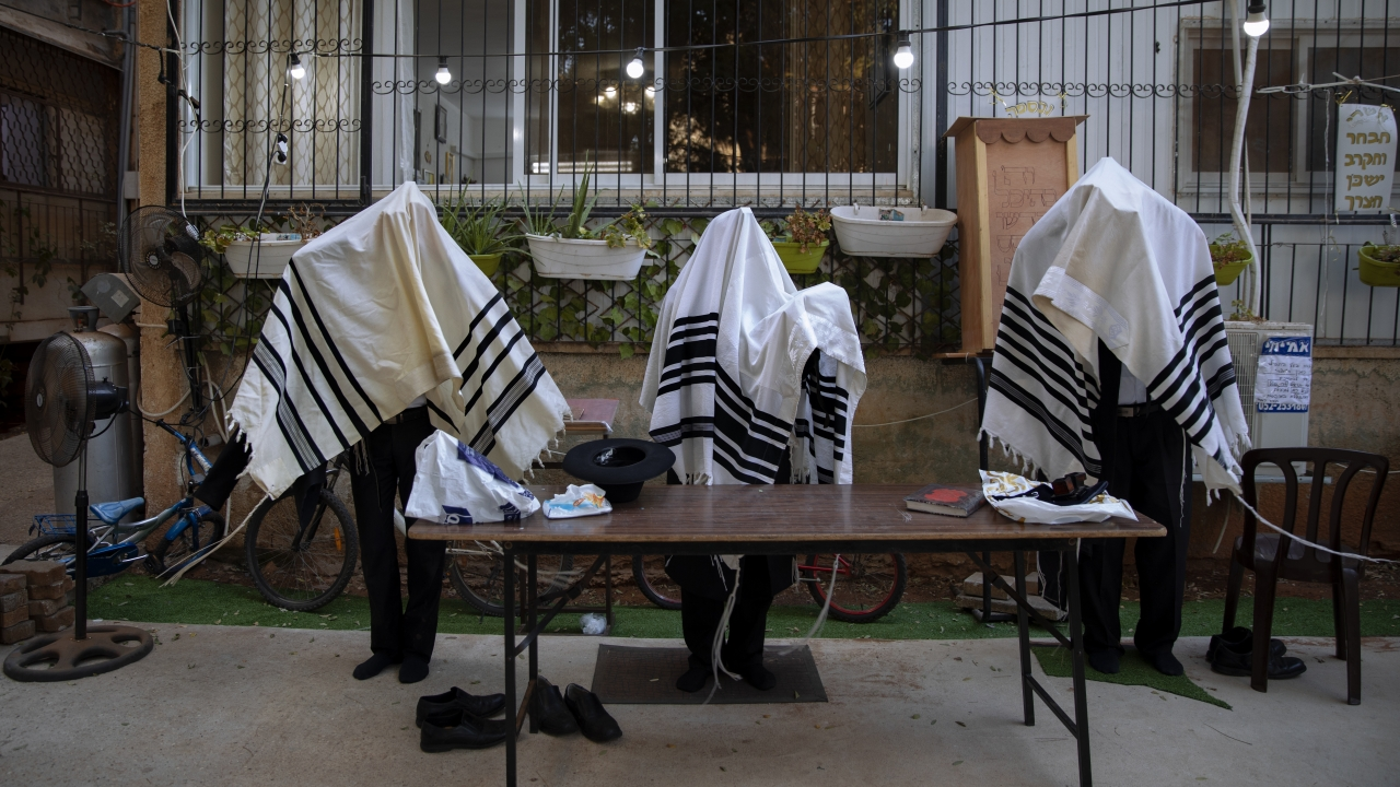 Ultra-Orthodox Jews pray covered in prayer shawls in divided sections which allow a maximum of twenty worshipers.