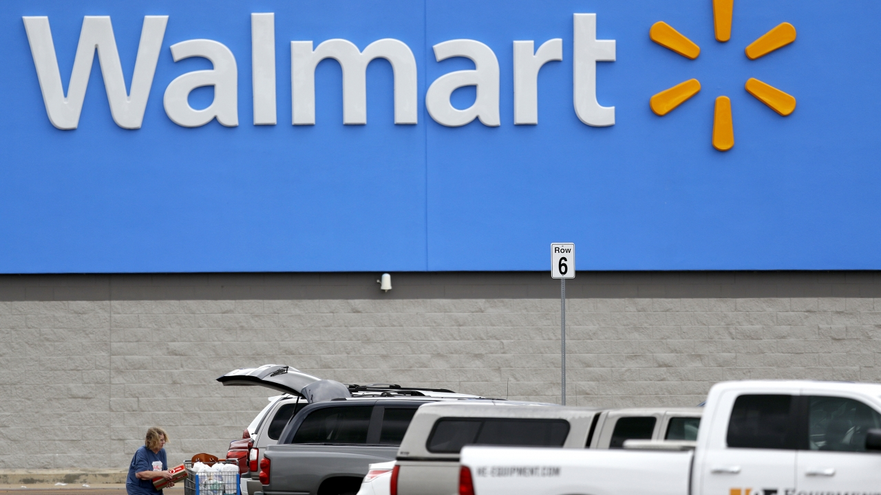 A woman pulls groceries from a cart to her vehicle outside of a Walmart store
