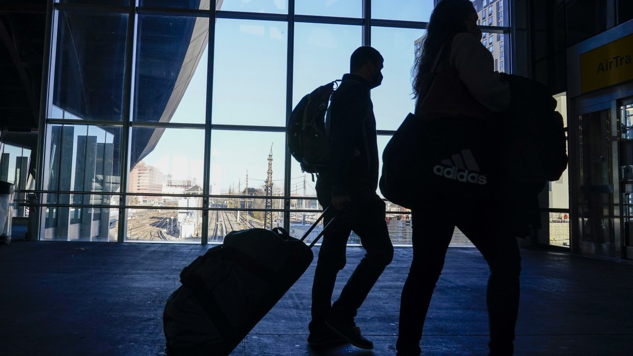 Travelers walk toward the AirTrain to JKF International Airport.