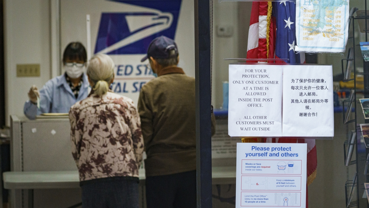 Customers speak with an Post Office employee in Los Angeles, California