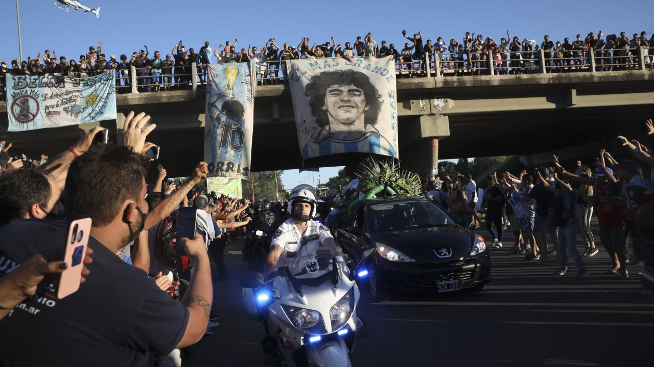 Mourning fans wave at the caravan carrying the remains of Diego Maradona to his resting place in Buenos Aires, Argentina.