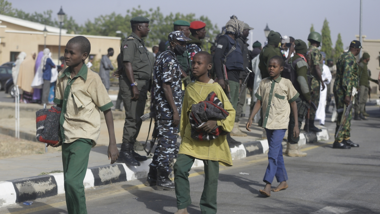 A group of schoolboys are escorted by Nigerian military and officials following their release after they were kidnapped.