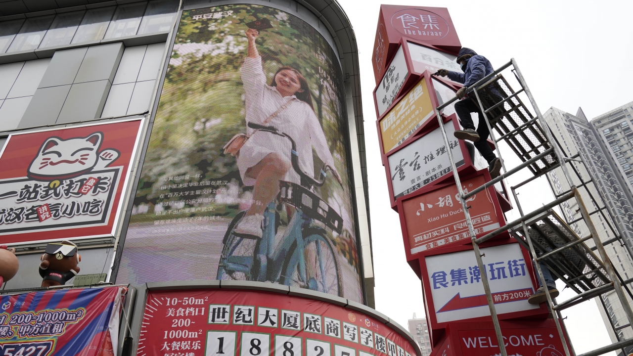 Workers clean up signboards outside a retail center in Wuhan in central China's Hubei province