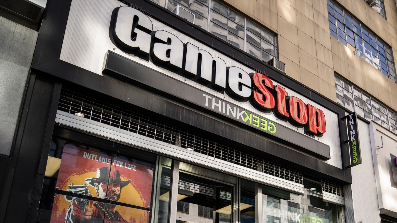 Pedestrians at a GameStop storefront.