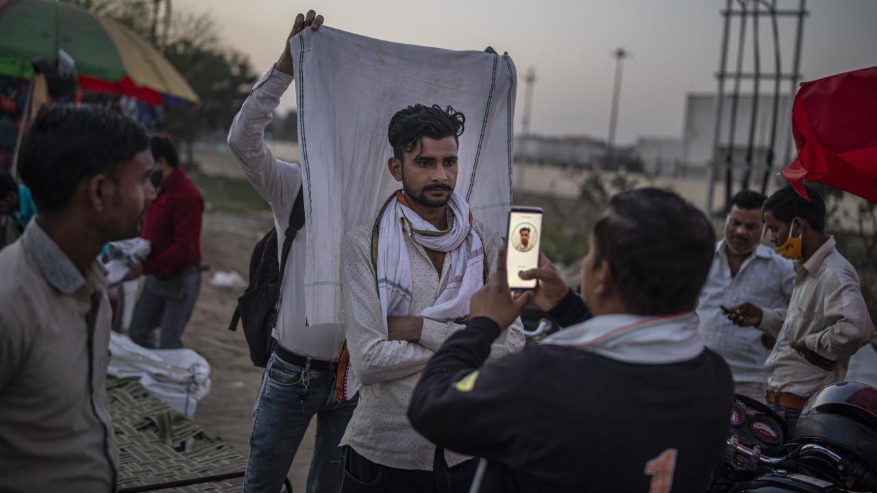 A roadside SIM card vendor takes a mugshot of a customer in New Delhi, India
