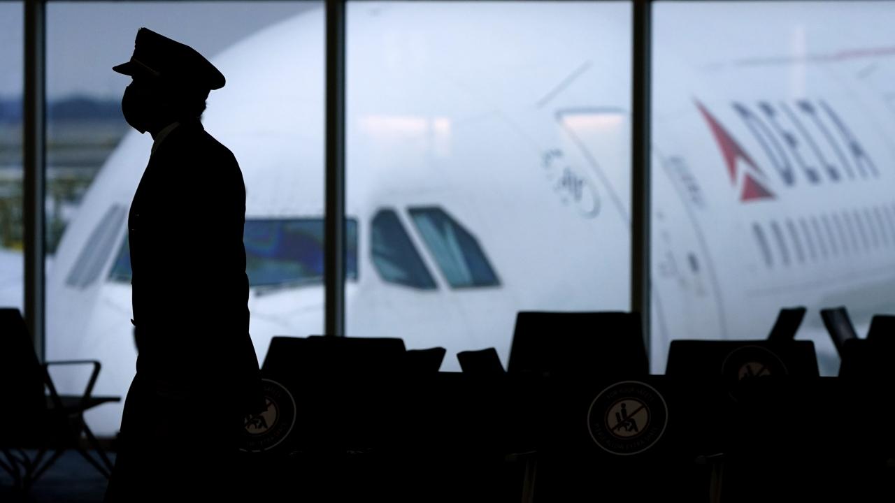 A pilot walks past a parked Delta Air Lines plane