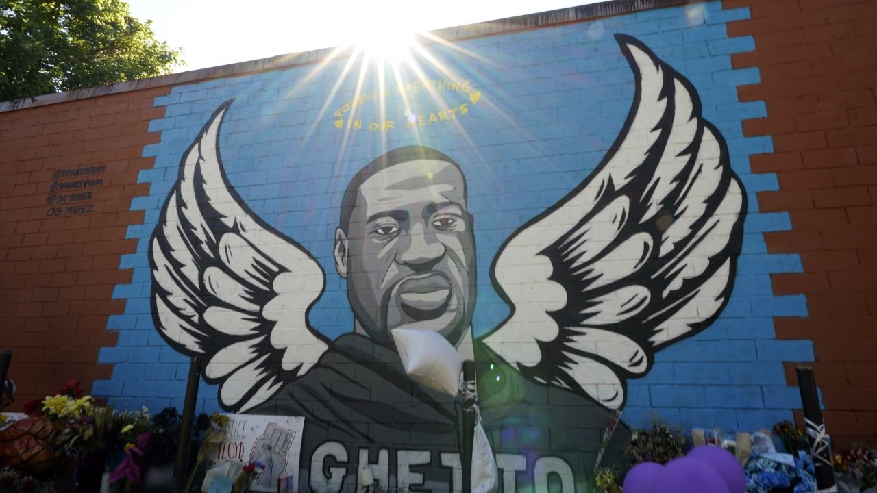 the sun shines above a mural honoring George Floyd