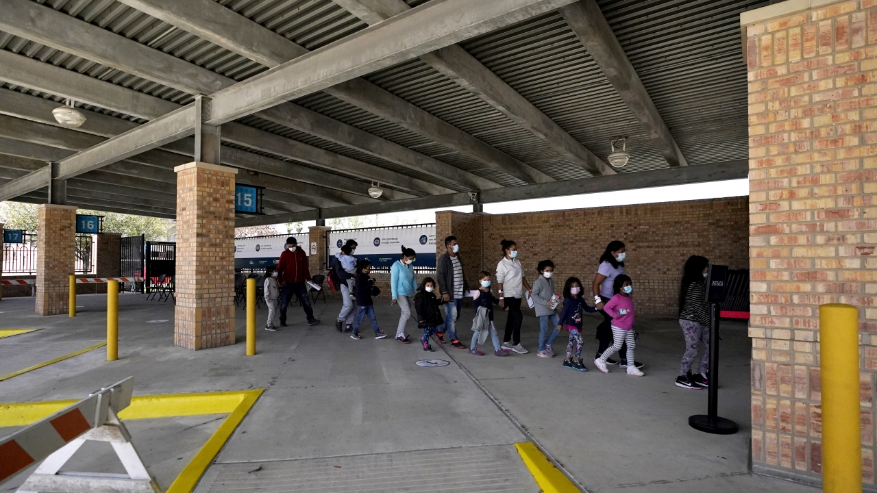 Migrants stand in line after being released from U.S. Customs and Border Protection custody at a bus station