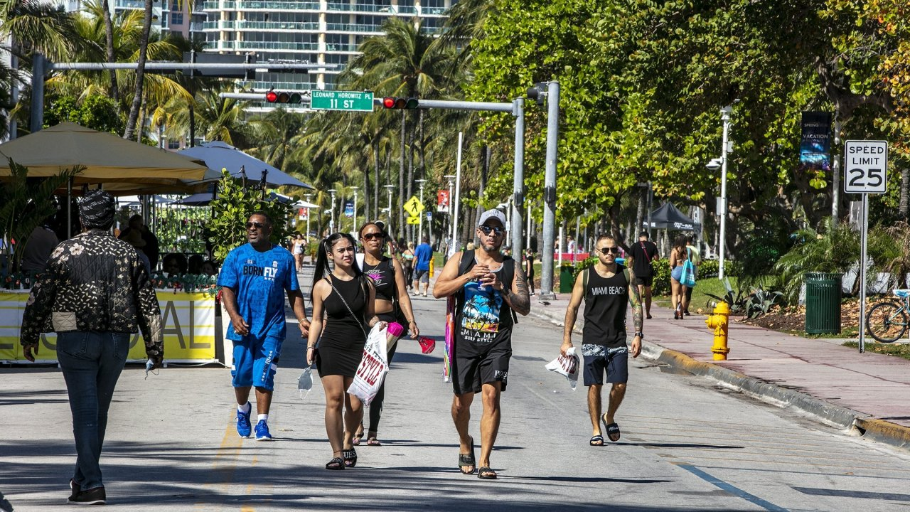 People walk to the beach in Miami, Florida as officials impose a state of emergency.