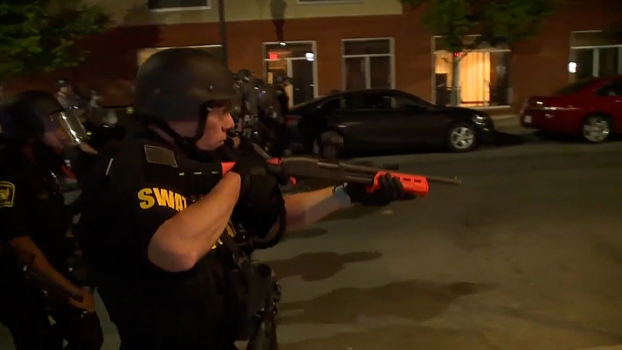 A SWAT officer points a shotgun at night while working the streets