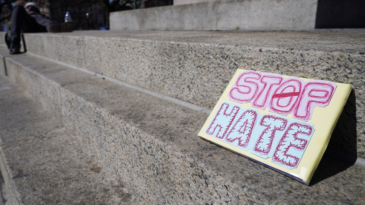 A sign is seen at the Logan Square Monument in Chicago, Saturday, March 20, 2021.