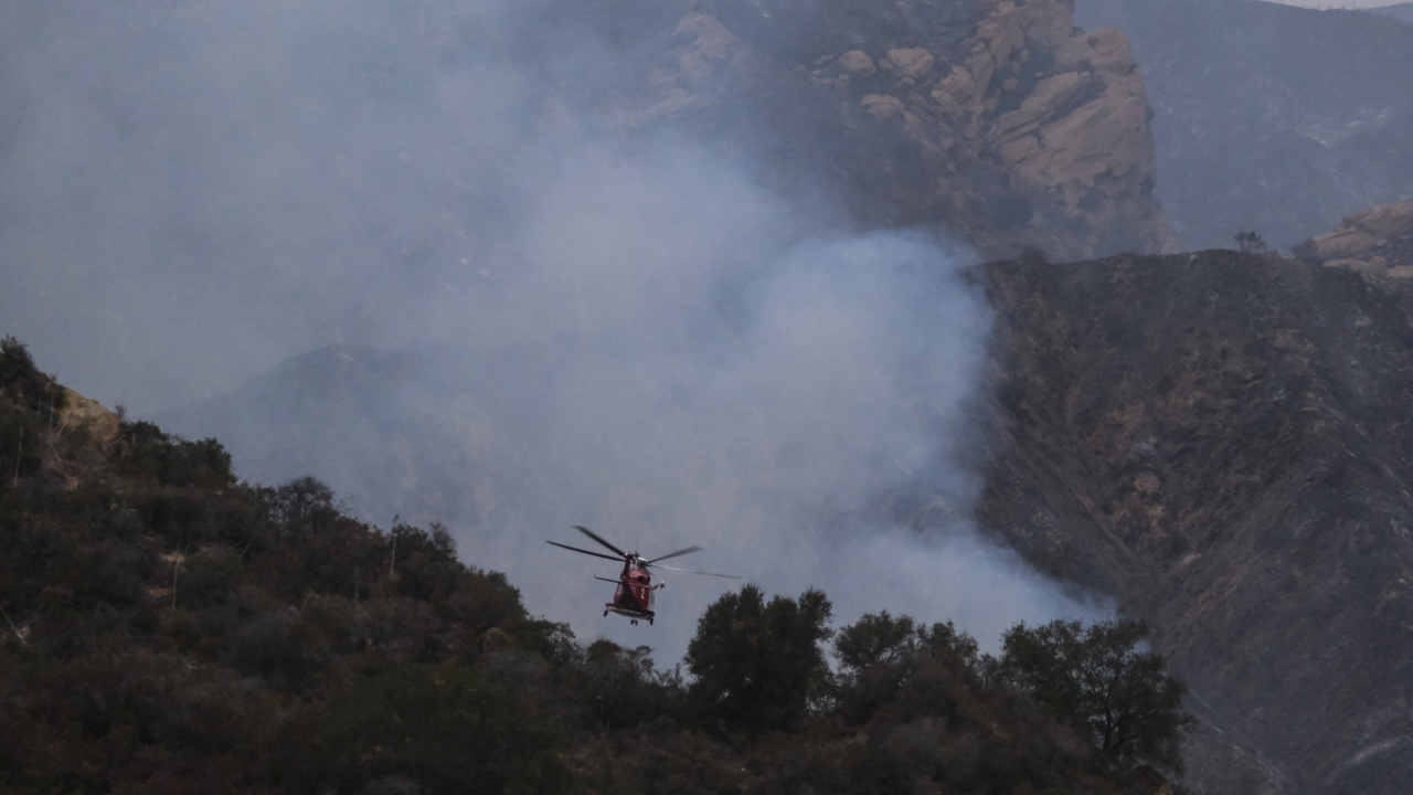 A firefighting helicopter prepares to drop water onto a wildfire in the Pacific Palisades area of Los Angeles.