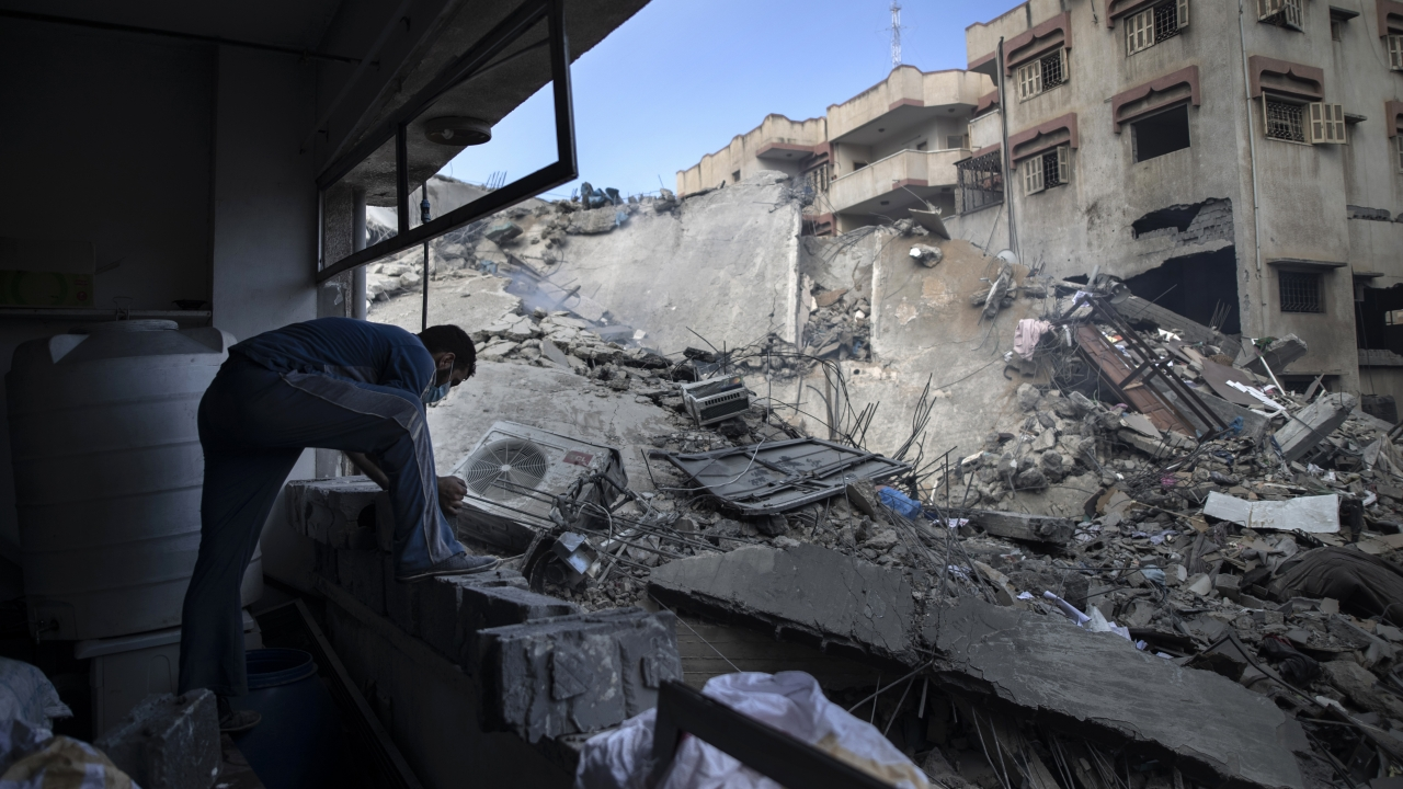 A Palestinian man inspects the damage of a six-story building which was destroyed by an early morning Israeli airstrike.